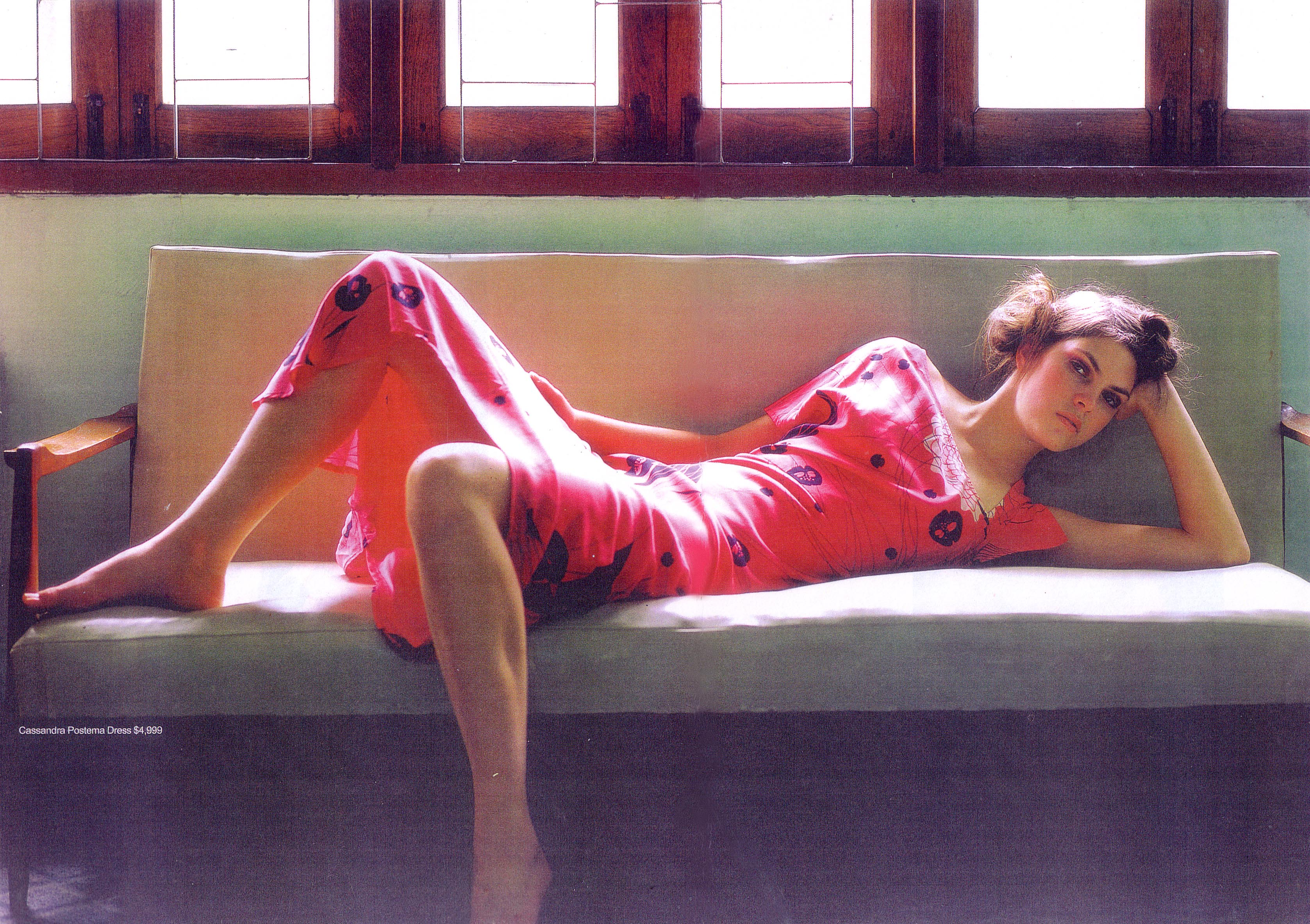 model in pink dress laying sofa